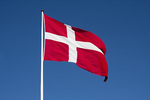 Det danske flag på hel stang med blå himmel i baggrunden.
